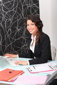 Female estate agent working at desk — Stock Photo