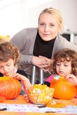 Woman helping her children carve pumpkins — Stock Photo
