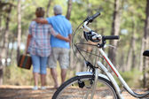 Couple taking a picnic to the woods by bike — Stock Photo
