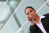 Businesswoman using a cellphone outside an office block — Stock Photo
