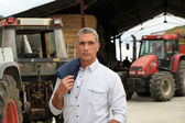 A farmer posing with his tractors — Stock Photo