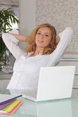 Young woman at a laptop with her arms stretched behind her head — Stock Photo