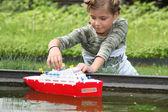 Schoolgirl playing with plastic boat — Stock Photo