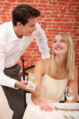 Couple in a restaurant with a gift — Stock Photo