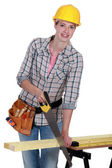Young female carpenter using saw — Stock Photo