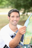 30 years old man watching a map in the forest — Stock Photo