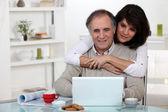 Un couple d'âge mûr en regardant un ordinateur portable. — Photo