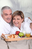Middle-aged couple having breakfast in bed — Stock Photo