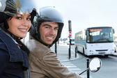 Couple on scooter in a crossroad — Stockfoto
