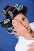 Woman wearing her hair in rollers and covering an eye — Stock Photo