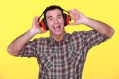 Happy man wearing earmuffs cancelling noise — Stock Photo