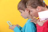 Children playing handheld video games — Stock Photo