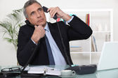 Businessman answering ringing telephones — Stock Photo