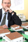 Pensive architect sat with model housing project — Stock Photo