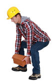 Tradesman lifting shingles — Stockfoto