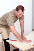 A handyman bending a covering — Stock Photo