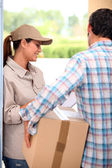 Man signing for a parcel at the front door — Stock Photo