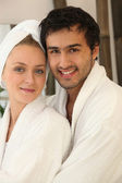 Portrait of young couple all smiles wearing bathrobe — Stock Photo