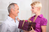 Young woman giving a gift to an older man — Stock Photo