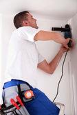 Hombre de perforación agujero en el techo — Foto de Stock