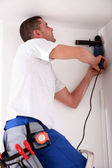Man drilling hole in ceiling — Stock Photo