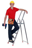 Man with drill standing on ladder rung — Stock Photo