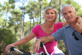 Older couple riding bikes in the countryside — Stock Photo