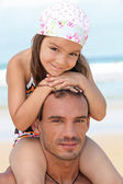 Little girl sitting on father's shoulders on the beach — Stock Photo
