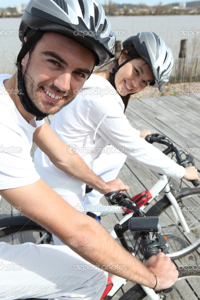 Young couple cycling alongside a river — Stock Photo #8380183