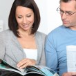 Couple reading magazines — Stock Photo