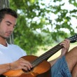 Stock Photo: Mplaying guitar under tree