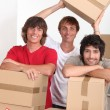 Three young in a room full of cardboard boxes — Stock Photo #8390387