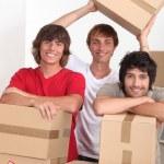 tre barn i ett rum fullt av kartonger — Stockfoto