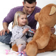 A little girl playing doctor with her teddy bear. — Stock Photo #8390404