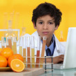 Little boy analyzing oranges in the laboratory — Stock Photo