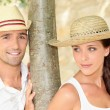 Couple wearing straw hats — Stock Photo