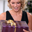 Stock Photo: Young womdelighted to receive prettily wrapped Christmas present