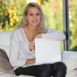 Blond girl sat at home with laptop computer - Stock Photo