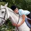 Young woman hugging her horse — Stockfoto