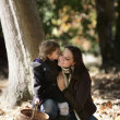 Little girl kissing her mum in woods — Stock Photo
