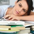 Stock Photo: Tired student leaning on a pile of books