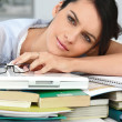 Tired student leaning on a pile of books — Stock Photo #8394614