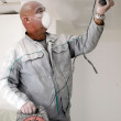 Man sanding a plasterboard ceiling — Stock Photo