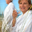 Couple relaxing by the sea - Stock Photo