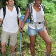 An interracial couple mountain hiking. — Stock Photo