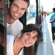 Foto Stock: Couple leaning out of tram door at station