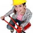 Woman with nippers sitting on toolbox — Stock Photo