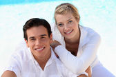 Couple sat by swimming pool — Stock Photo