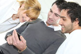 Three looking at mobile telephone screen — Stock Photo