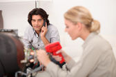 Female technician working while the client is talking on the phone — Stock Photo